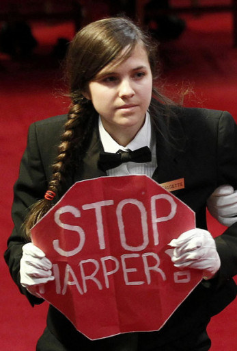 "A protester holds a sign reading ""Stop Harper"" is led from the room as Canada's Governor General David Johnston delivers the Speech from the Throne in the Senate chamber on Parliament Hill in Ottawa"